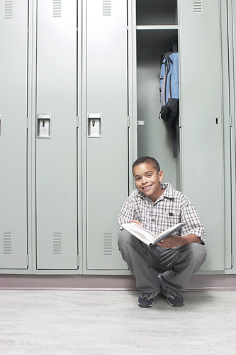 boy sitting in school locker