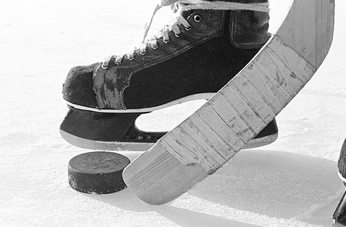 Photo of a hockey stick, puck and skate