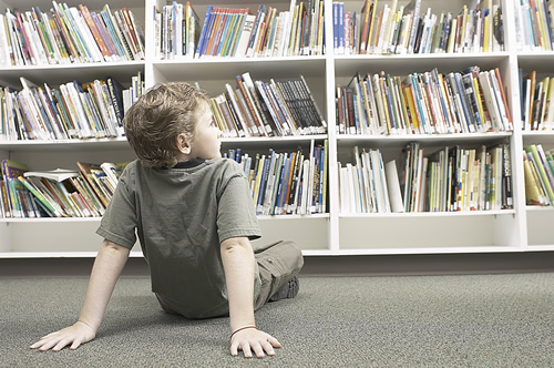 Boy looks at books on library bookshelves.