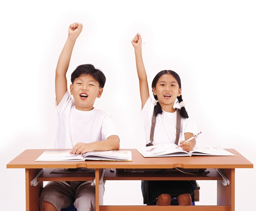 Boy and girl sitting at desk raising hands