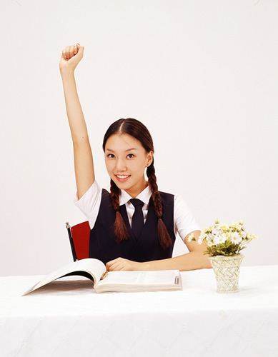 Girl with pigtails sitting in front of a book raising her hand
