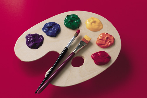 Image of paint palette with rainbow of colors and red background
