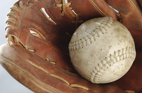 worn baseball in old glove