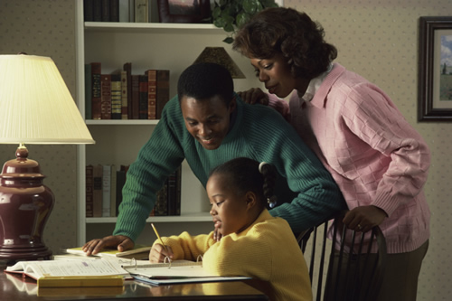 Picture of a mother and father helping daughter with homeworkr