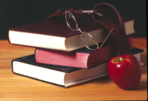 Three books, a pair of glasses and an apple on a desk.