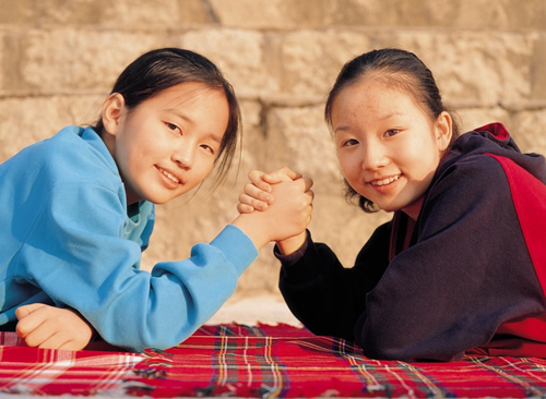 two middle school girls smiling and holding hands