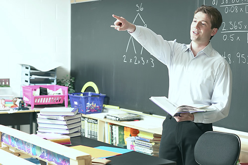 Teacher pointing towards the students in a classroom