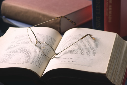 Photo of an open book with a pair of reading glasses on top